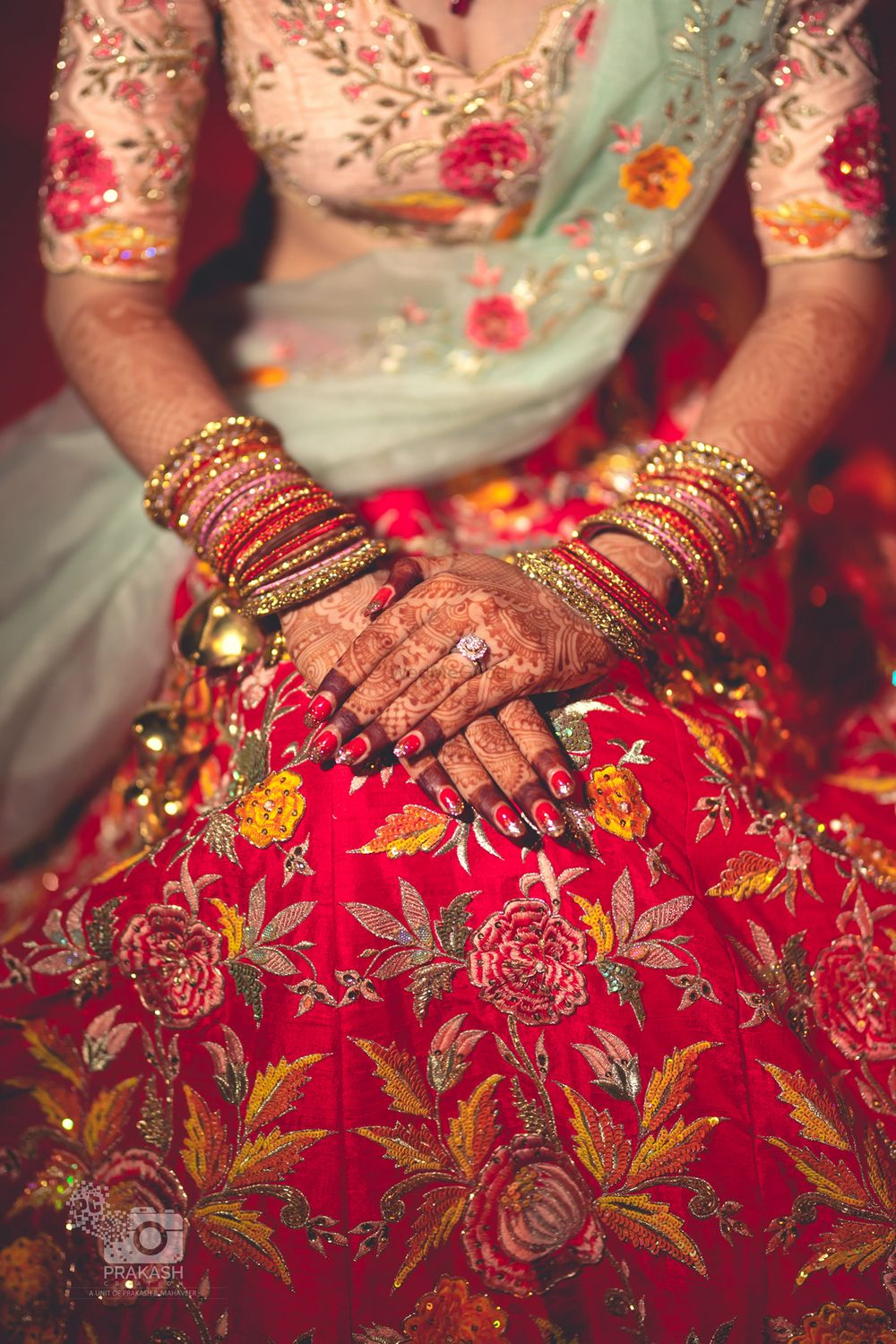 Photo of Bridal hands on floral embroidered lehenga