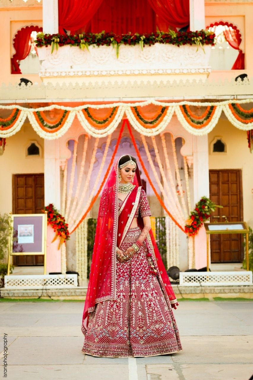 Photo of A bride in a red lehenga with double dupatta on her wedding day