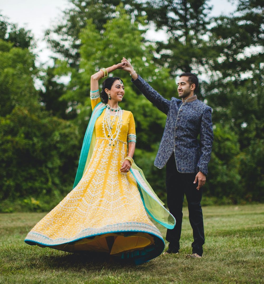 Photo of Bride twirling in yellow anarkali with aqua border