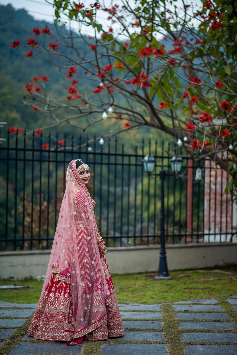 Photo of Red lehenga with contrasting pink dupatta on the head