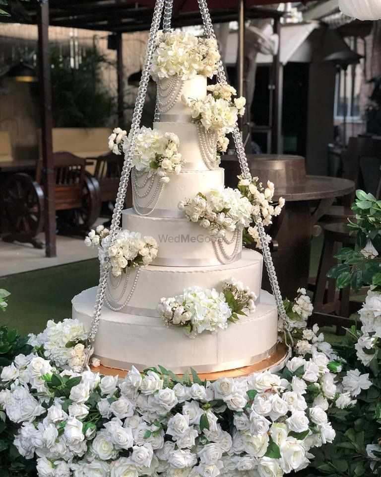 Photo of White wedding cake on a swing with florals