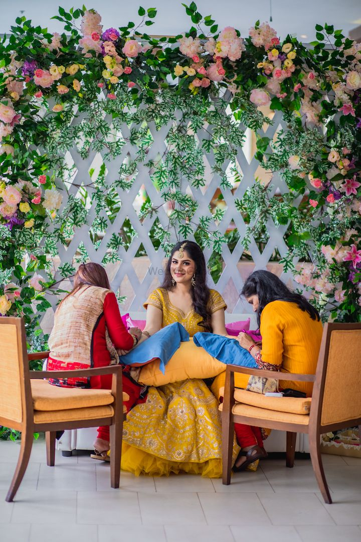 Photo of Bride getting her mehendi put against backdrop