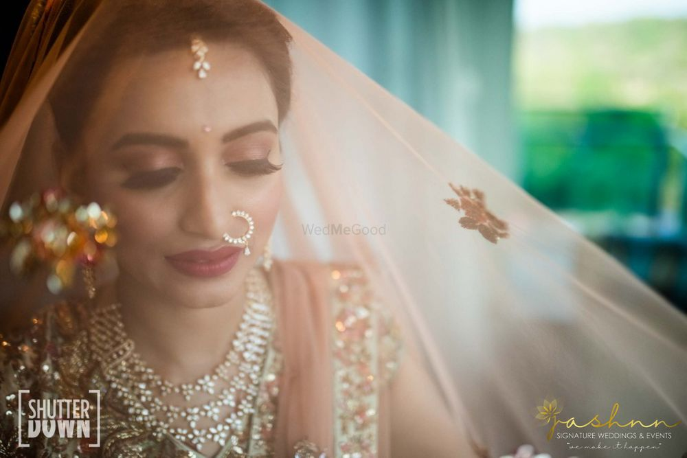 Photo of bridal portrait with a veil out of peach dupatta