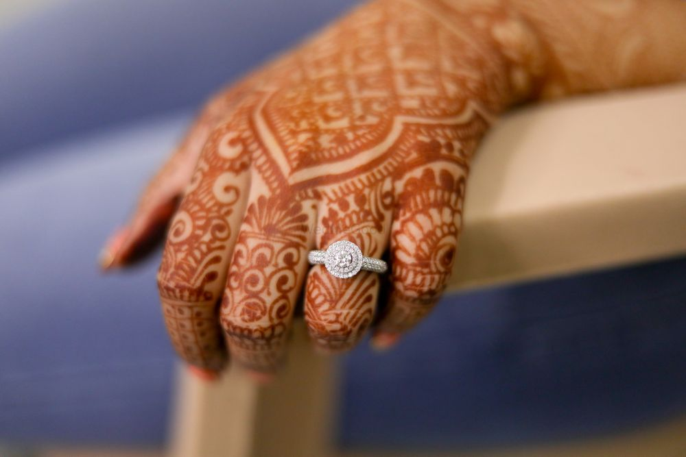 Photo of bridal hands with mehendi and engagement ring shot