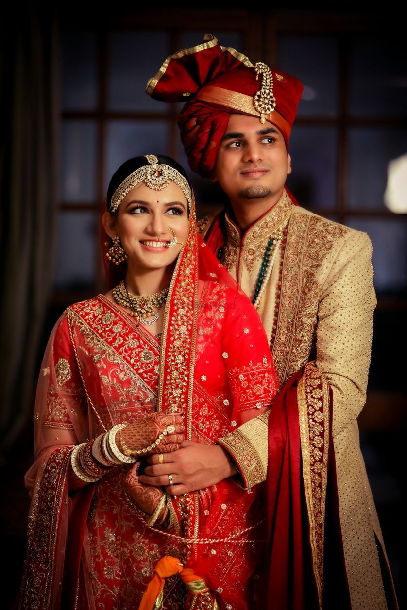 Photo of bright and happy couple shot with the bride in red