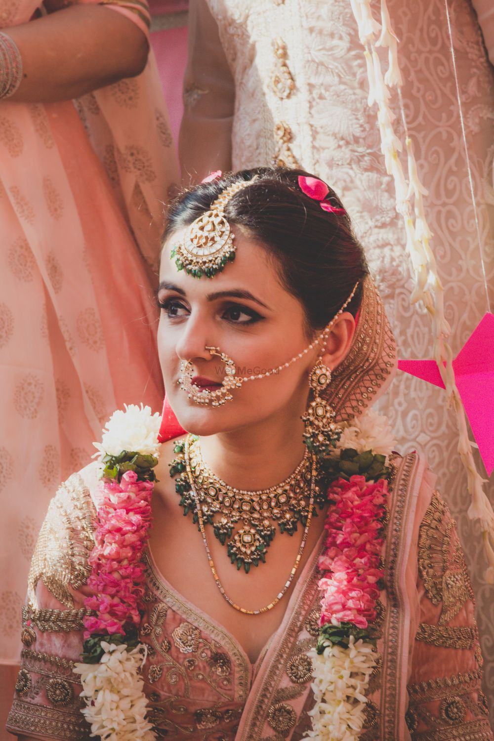 Photo of bridal jewellery with green beads and a nath