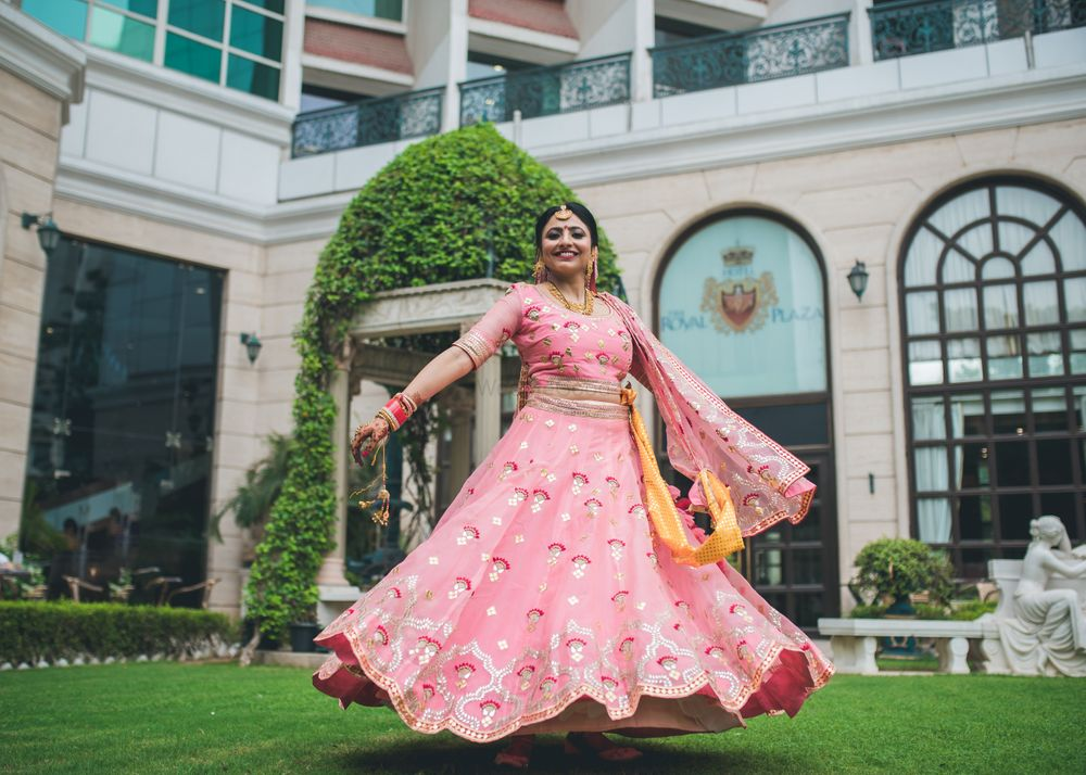 Photo of bride twirling in candy pink lehenga on wedding day