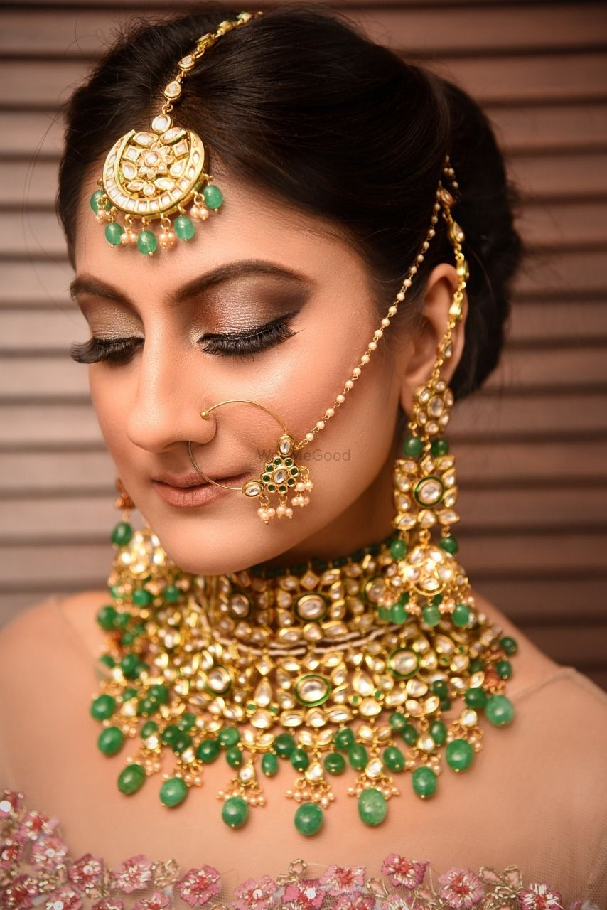 Photo of Closeup of a bride wearing a choker and a light nath with green beads