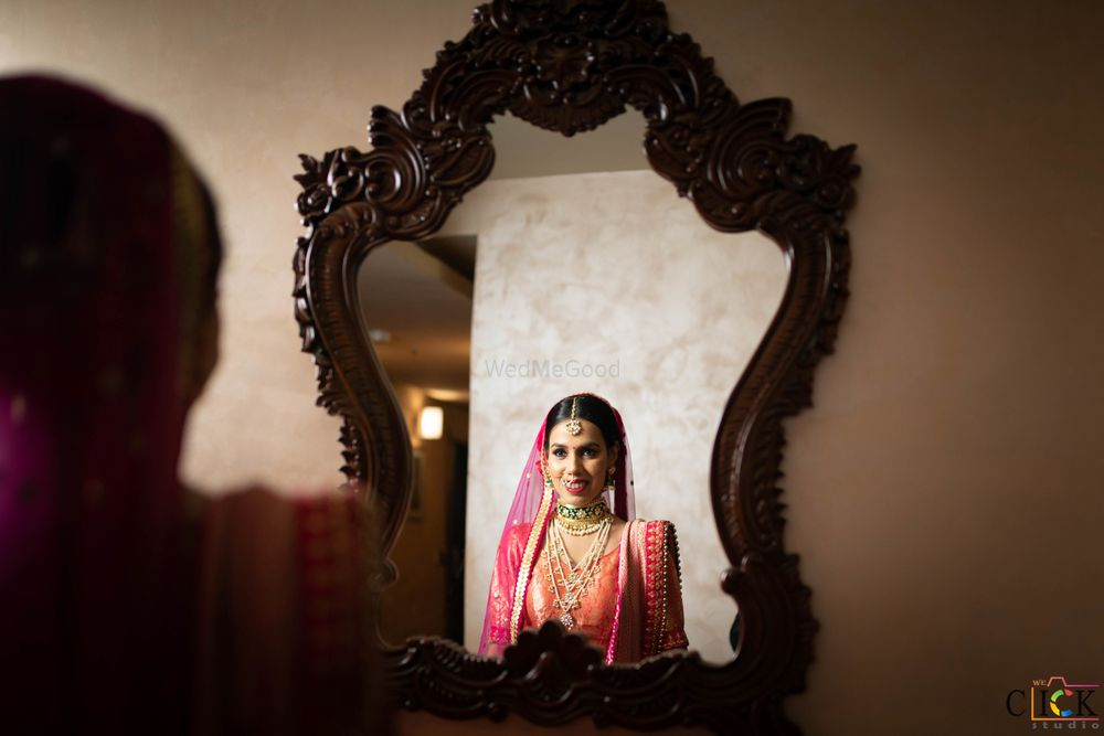 Photo of bride looking at mirror after getting ready on wedding day