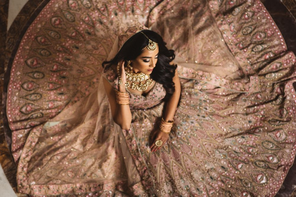 Photo of bride to be sitting with onion pink flared lehenga