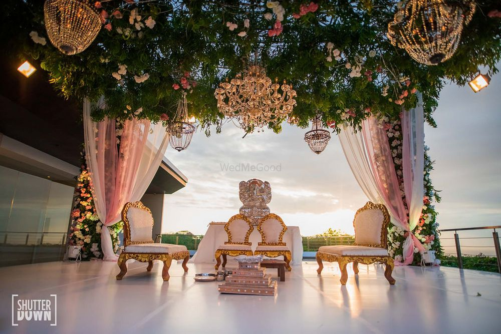 Photo of grand floral mandap decor idea with chandeliers