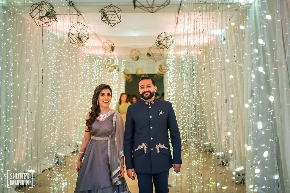 Photo of matching bride and groom entering cocktail with fairy lights