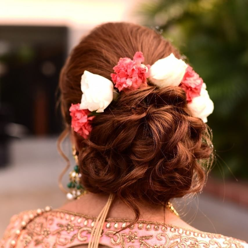 Photo of A bridal bun with flowers.