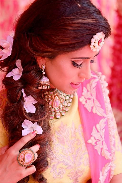 Photo of bridal mehendi look with side braid with flowers and floral jewellery