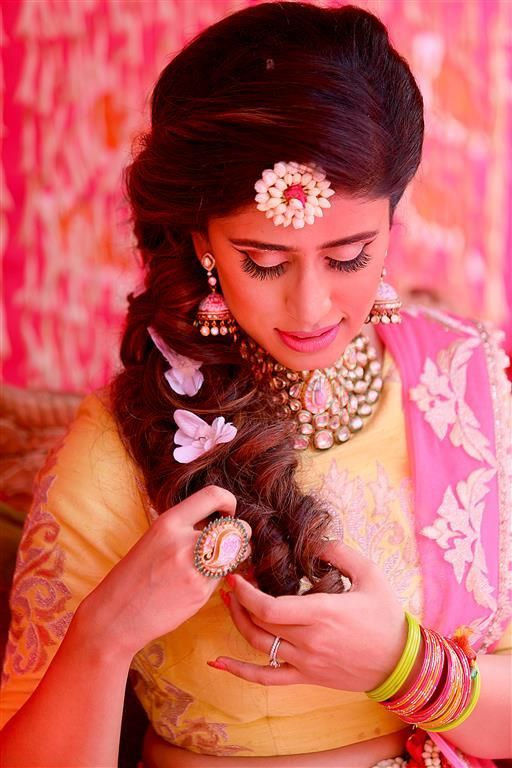 Photo of mehendi bridal look with hairstyle with flowers