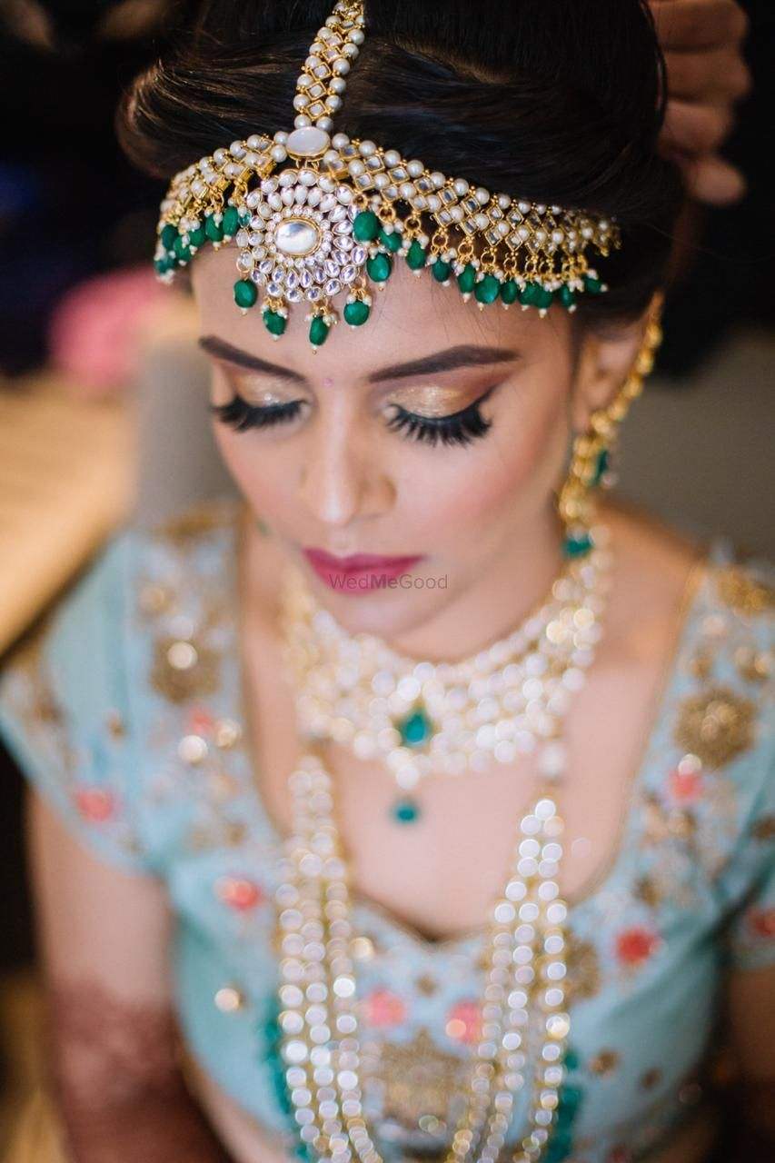 Photo of bride with gold eye makeup and green kundan mathapatti