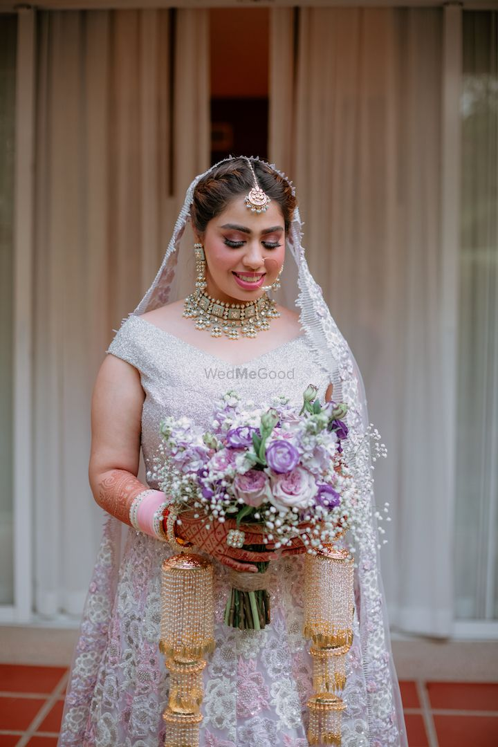 Photo of simple bridal look with bride holding a purple bouquet