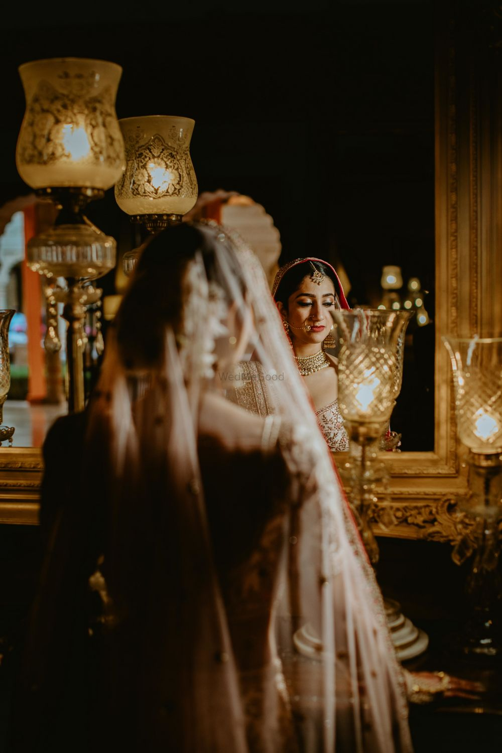 Photo of bride looking at herself in the mirror