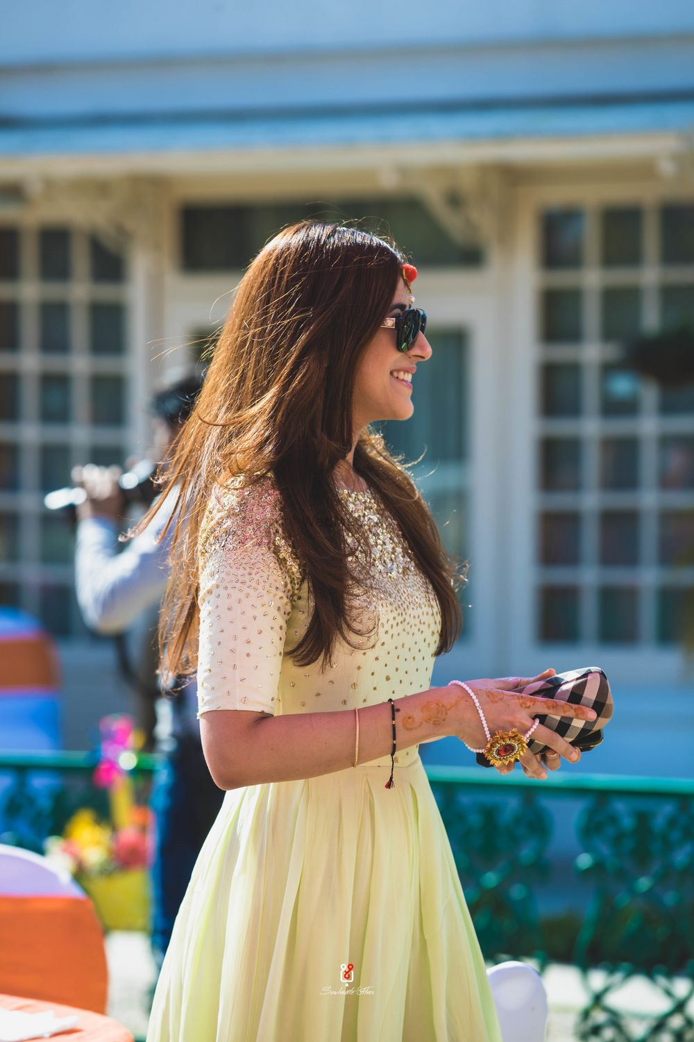 Photo of A portrait clicked of the sister of the bride in a yellow outfit and wearing sunglasses