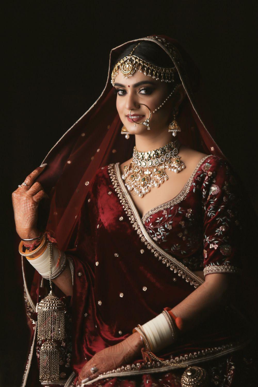 Photo of Portrait of a bride in maroon velvet lehenga