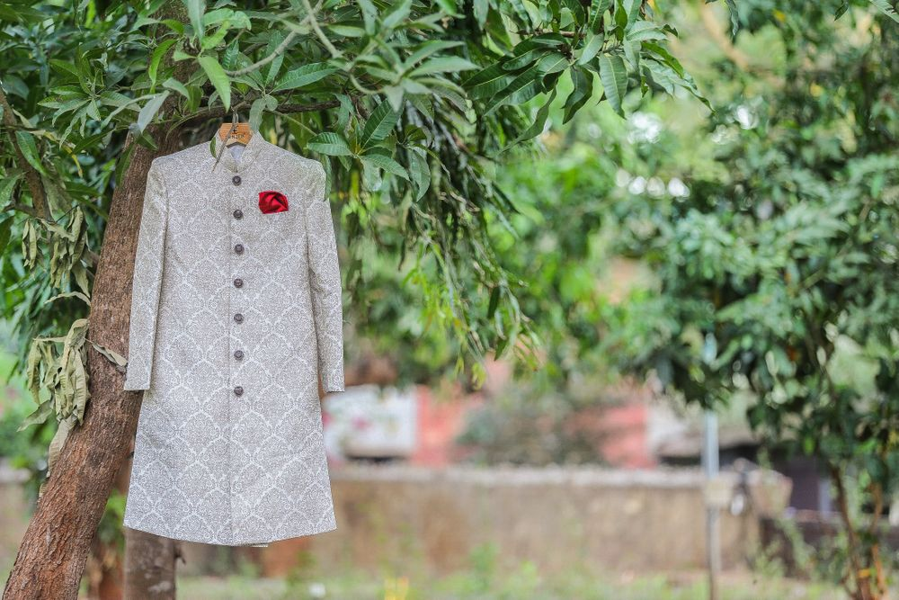 Photo of White Sherwani with Red Pocket Square on a Hanger