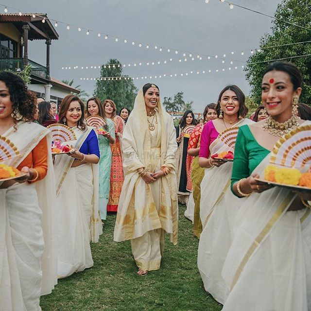 Photo of Bride entering with bridesmaids dressed in coordinated outfits