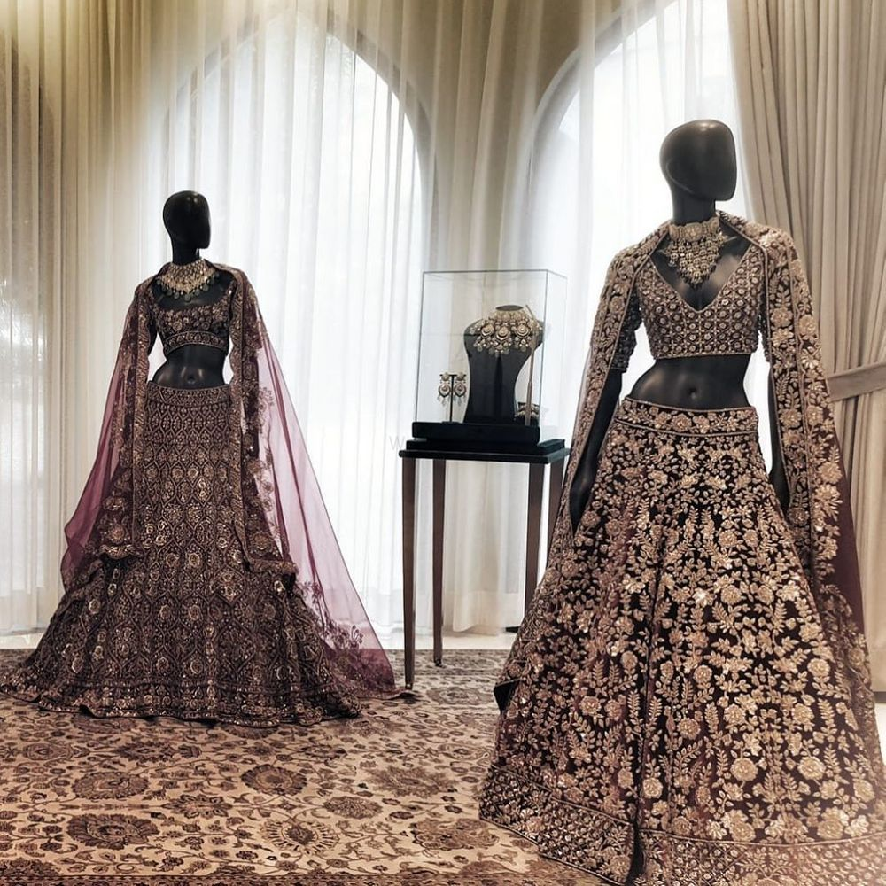 Photo of Maroon & gold and Plum & gold heavy bridal lehengas with detailed blouse and net dupatta.