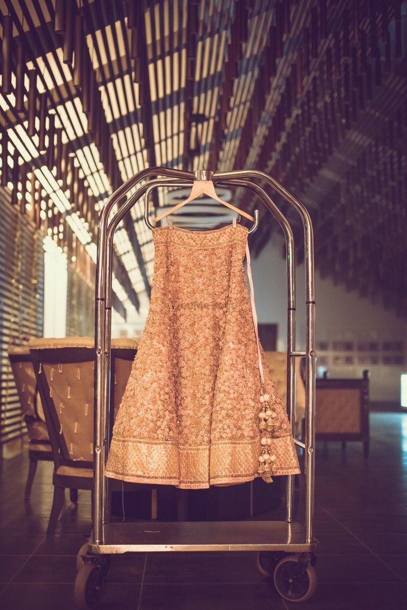 Photo of Dull Gold Bridal Lehenga with Latkans on a Hanger