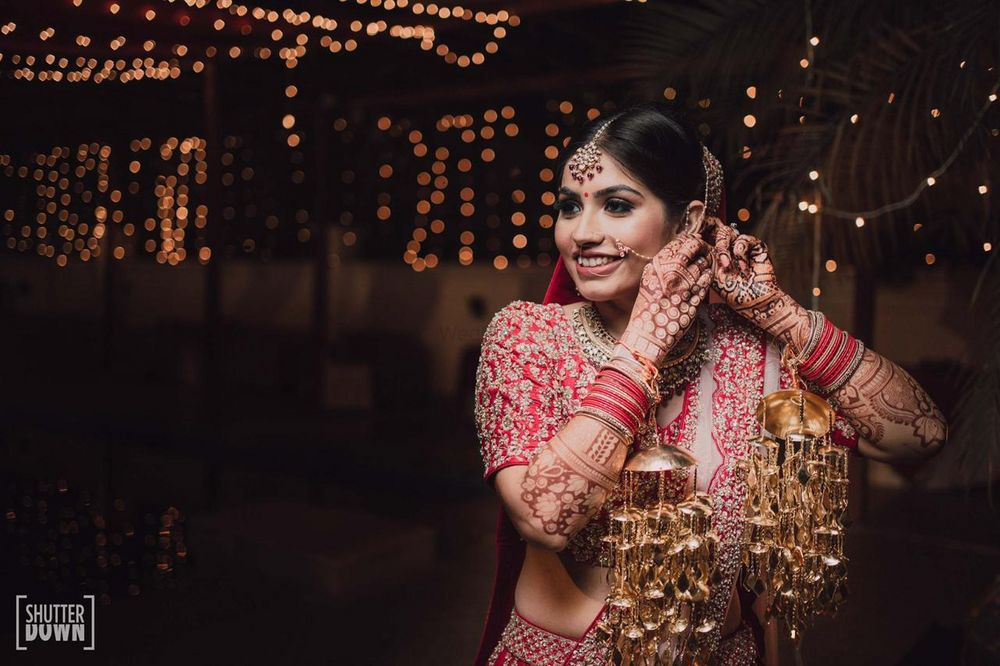 Photo of Bride posing while fixing her wedding jewellery