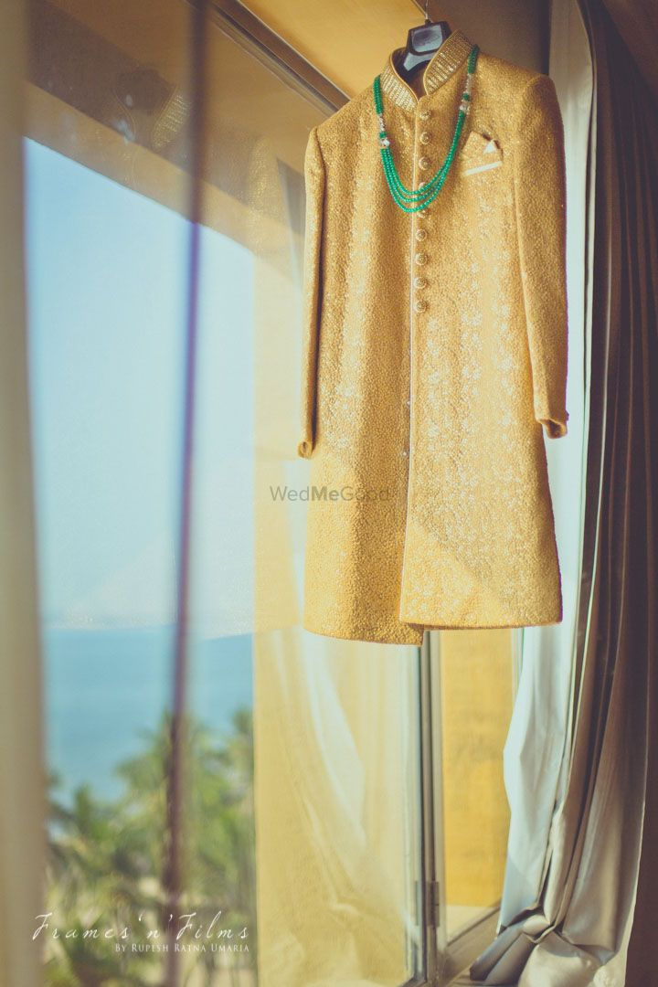 Photo of Gold Sherwani on a Hanger with Green Haar