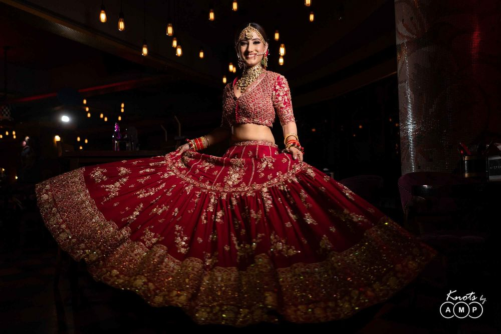 Photo of Bride twirling in red flared lehenga