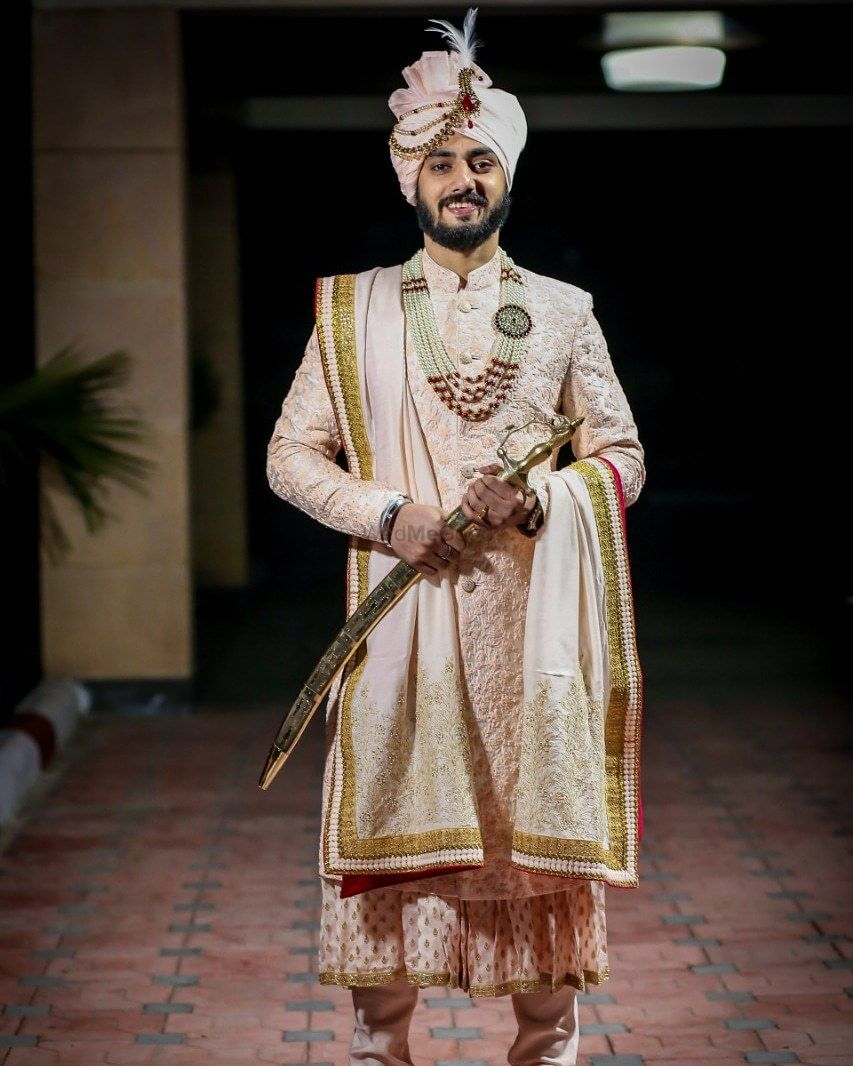 Photo of royal groom look with pastel sherwani and necklace