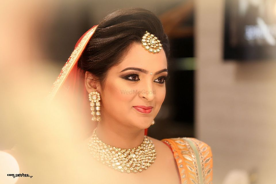Photo of Bride wearing Gold Maangtikka and Peach Dupatta