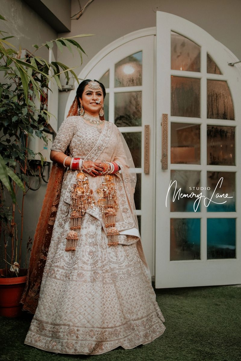 Photo of Bride wearing a white lehenga with silver detailing on her wedding day.