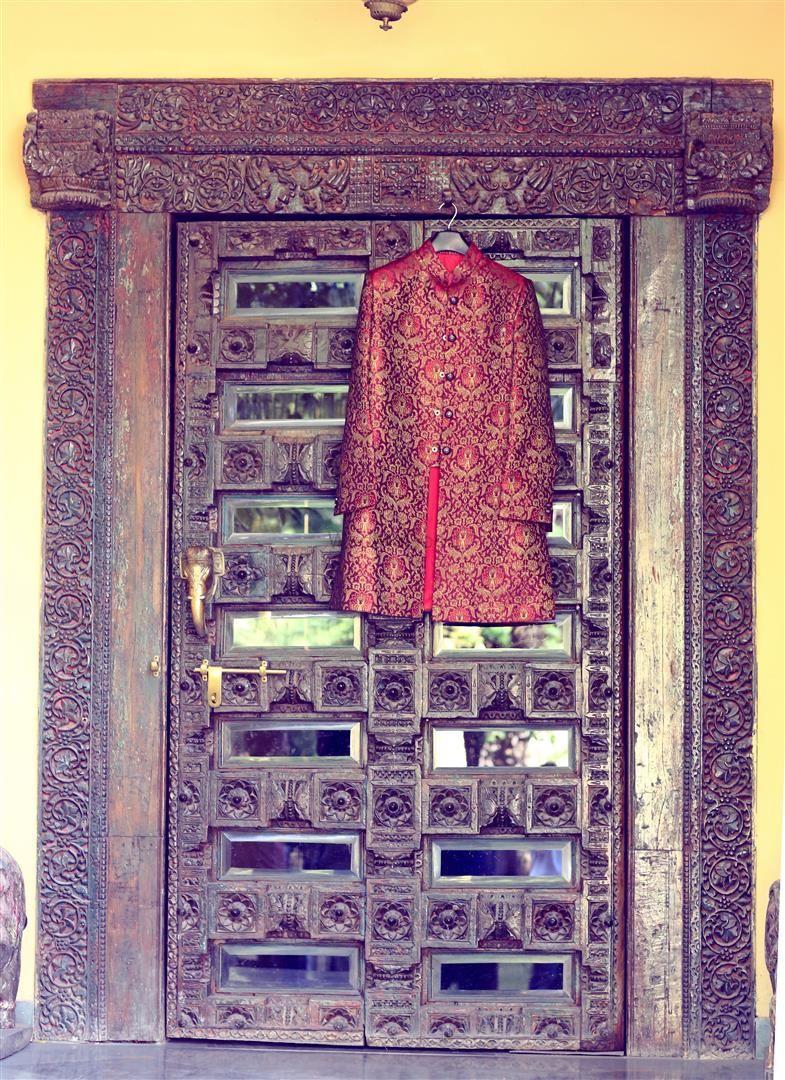 Photo of Deep Red Sherwani Hung on Royal Door