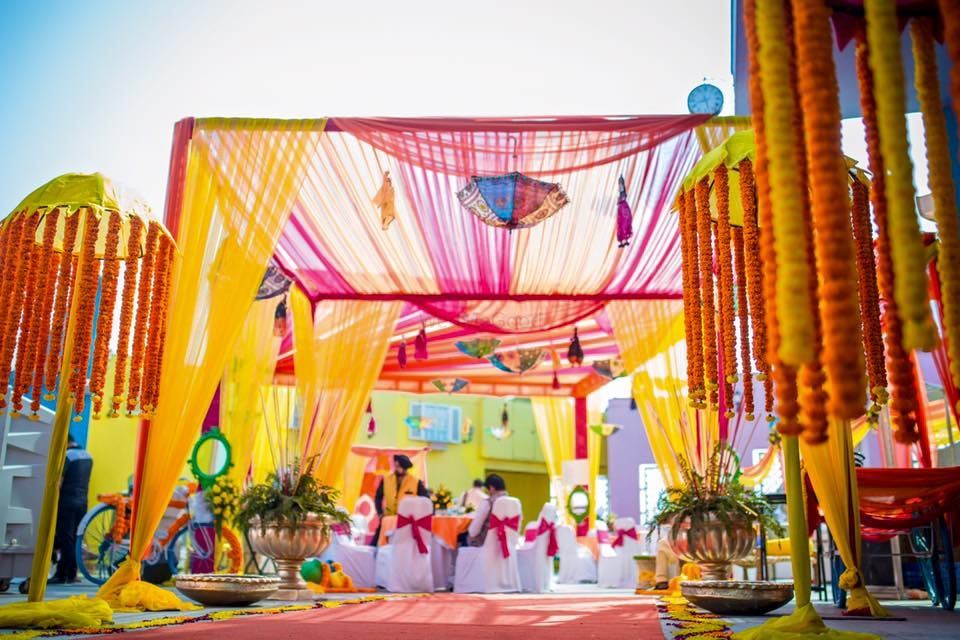 Photo of Colorful Mehendi Decor Tent with Props and Florals