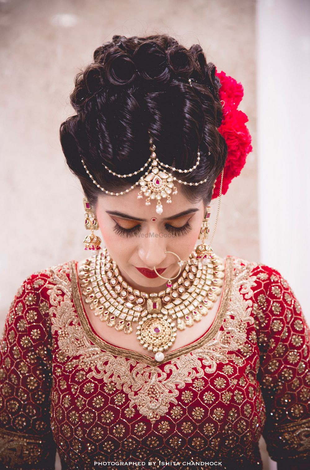 Photo of Curly Bun Bridal Hairstyle with Red Flowers on Side