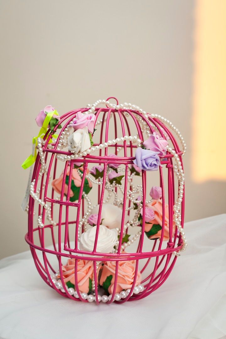 Photo of birdcage packaging with flowers and sweet treats