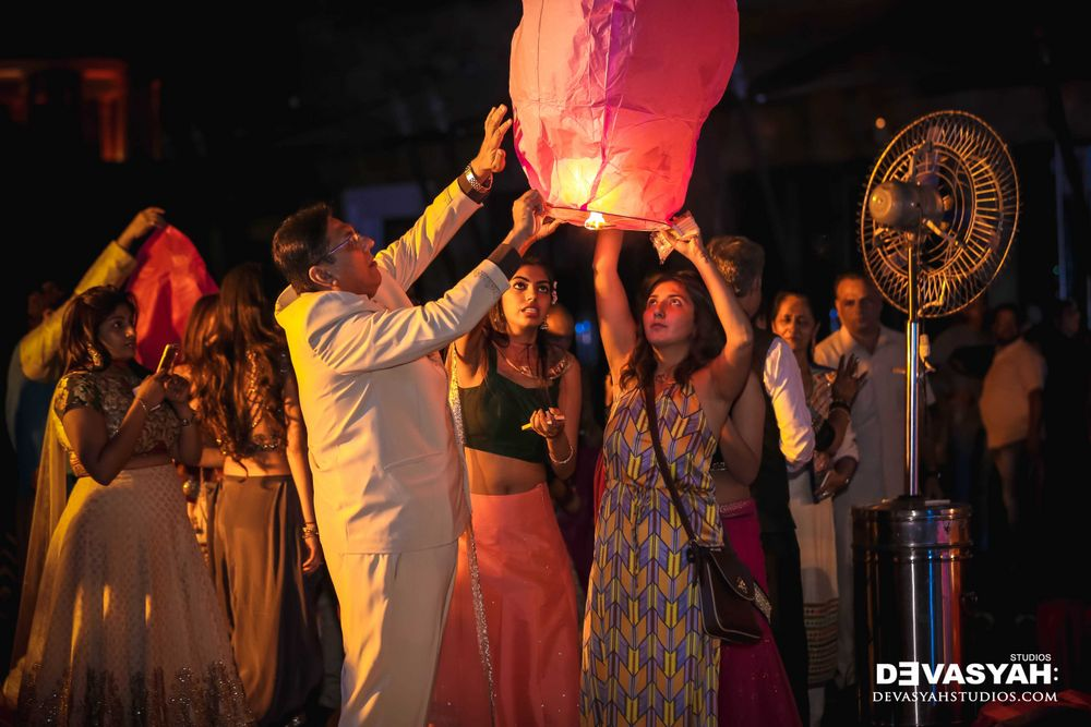 Photo of Guests Launching Flying Paper Lanterns at Wedding