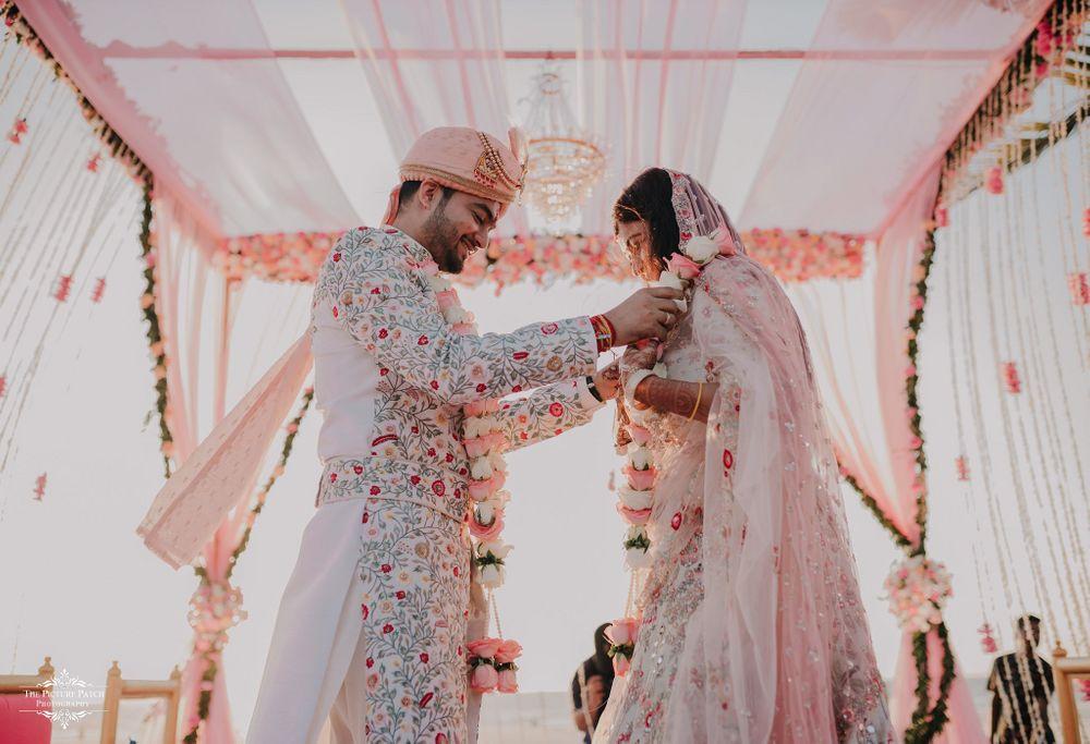Photo of pastel wedding jaimala shot by the beach