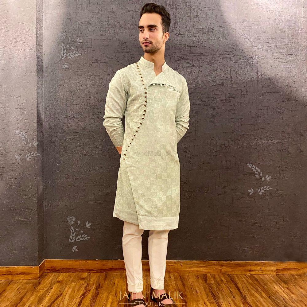 Photo of White kurta pyjama with overlapping button details.