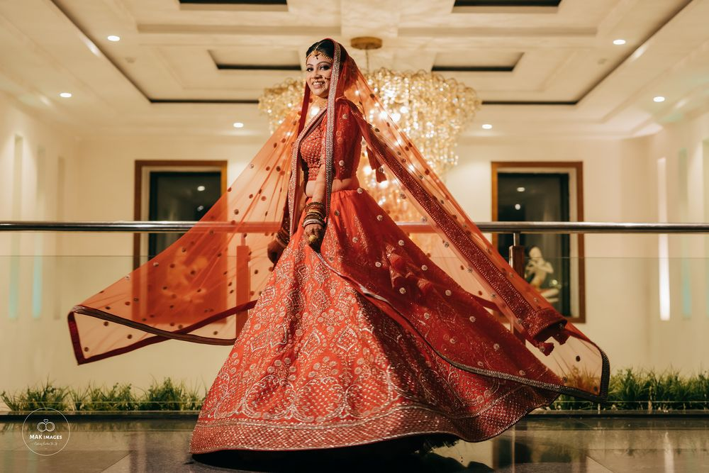 Photo of Twirling shot of a bride dressed in a red lehenga.