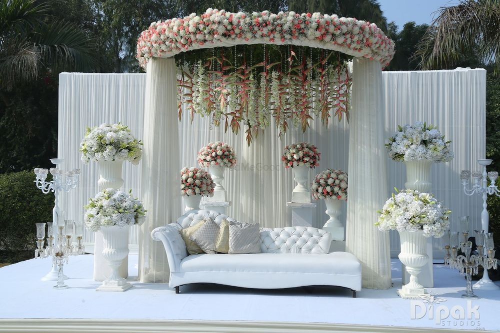 Photo of All white stage with floral decorations.