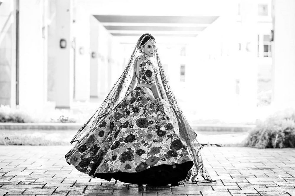Photo of twirling bride shot in sabyasachi lehenga black and white