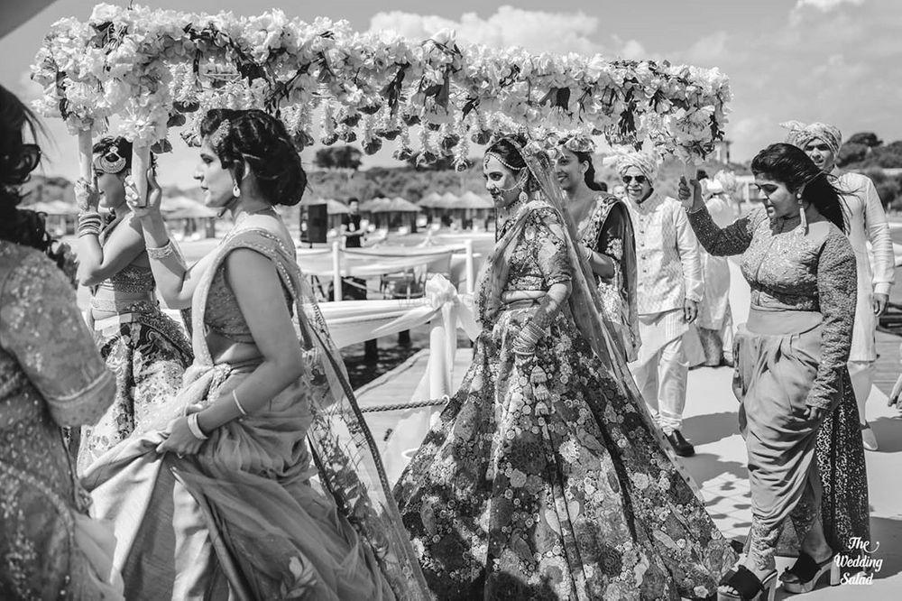 Photo of black and white bridal entry shot under phoolon ki chadar