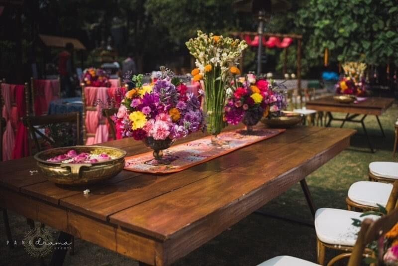 Photo of table setting for backyard mehendi on rustic table