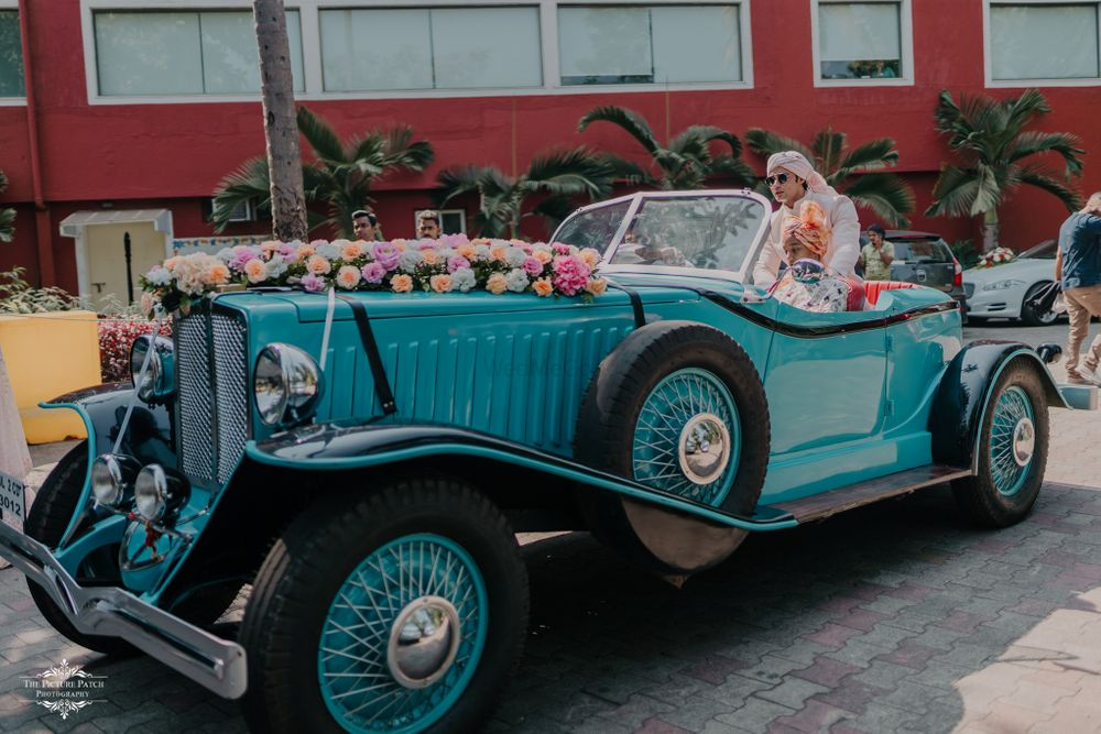 Photo of Groom entry on a vintage car.