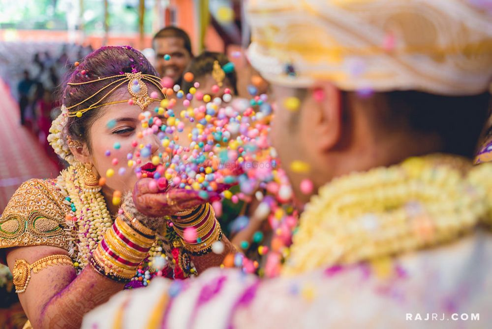 Photo of Bride Blowing Confetti Balls on Groom