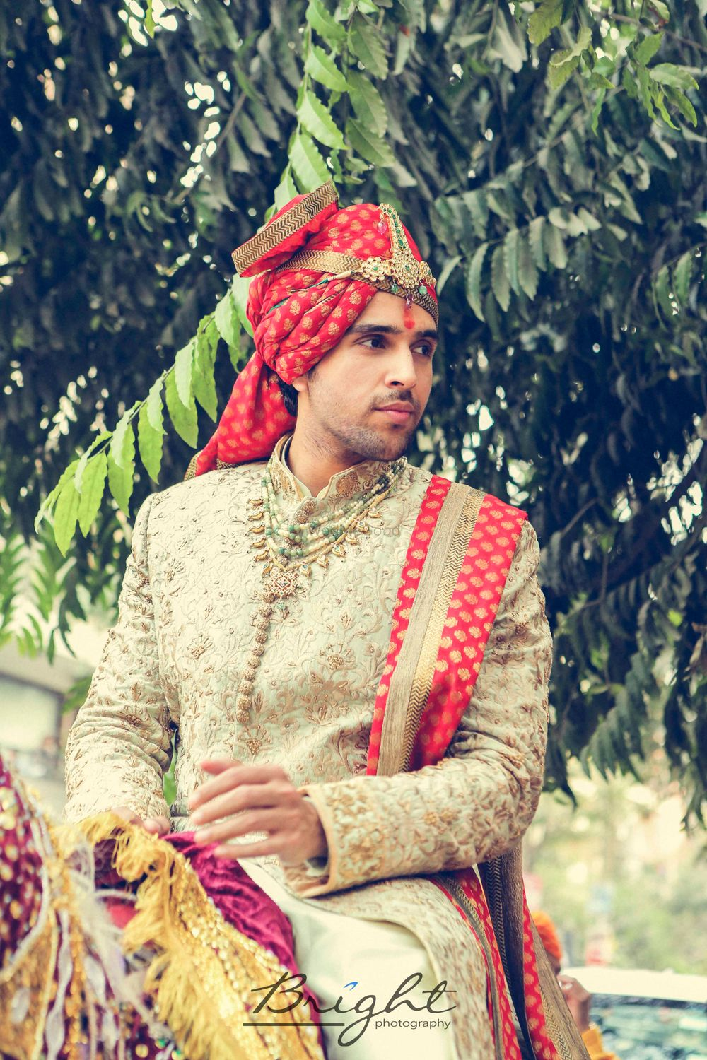 Photo of Off white and red embroidered sherwani with jewellery