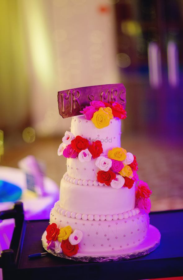 Photo of Colourful 4 tiered wedding cake with mr and mrs topper